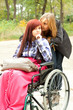 invalid girl on the wheelchair with friend outdoors