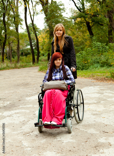 invalid girl on the wheelchair with nurse in the park