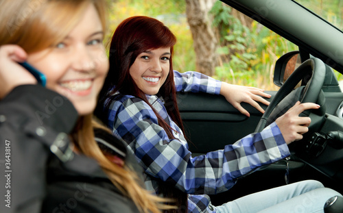 two young female friends driving in car