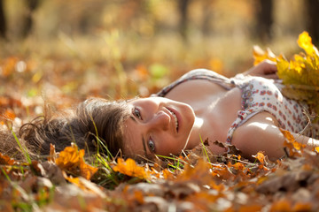 Young woman lies in oak leaves