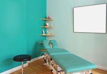 Massageliege mit leerer Texttafel an der Wand