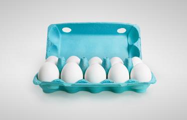 Ten white eggs in a carton box