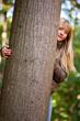 Mädchen versteckt sich hinter Baum