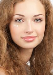 Beautiful woman applying moisturizing cream