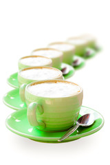 Green coffee cup placed in a row