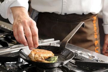 beim braten einer Perlhuhnkeule in der Restautantküche