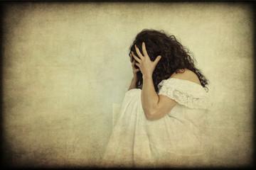 Donna che si copre il volto, stanca e disperata