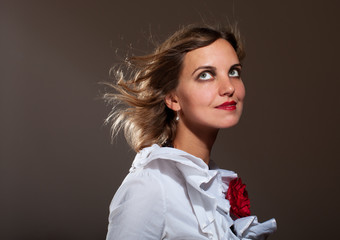 Daydreamed woman in white blouse with red flower