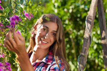 Happy woman in garden with flowers