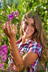 Glückliche Frau im Garten mit Blumen