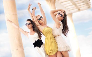 Three cheerful women wearing sunglasses