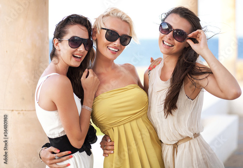 Three adorable women wearing sunglasses