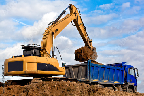 Backhoe loading a dump truck