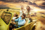 Fototapety Group of cheerful friends driving a cabriolet