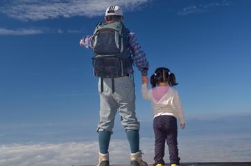 雲海の上に立つ男性と少女