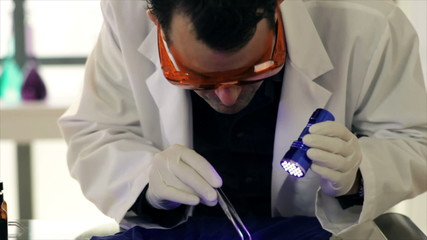 A CSI agent using a UV light to examine evidence.