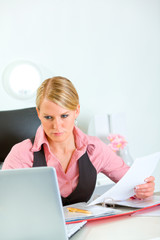 Serious business woman holding document and looking in laptop
