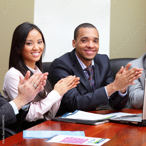 Multi ethnic business group greets you with clapping