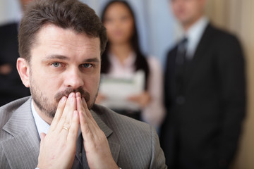Portrait of a worried businessman with his team behind