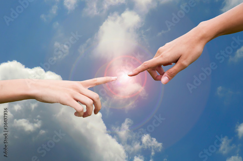 Fingers reaching to touch in a sky background