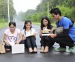 Group of Indian college students studying at the middle of road.