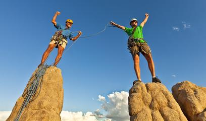 Rock climbing team reaching the summit.