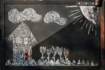 Child's picture drawn in chalk on a iron garage door