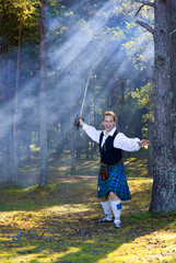 Screaming man in scottish costume with sword