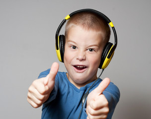 Young boy in headphones giving thumbs up sign
