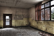Empty room with broken window and yellow tiled wall in an abando