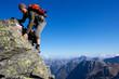 Young man climbing the mountain ridge