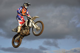 The spectacular jump moto racer on a motorcycle
