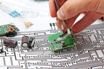 A hand hand with tweezers holding a electronic circuit board on
