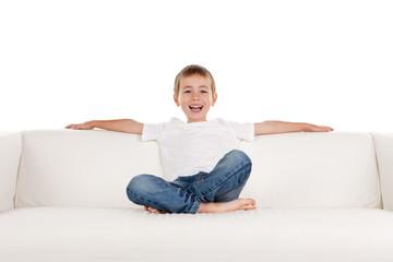 Happy boy relaxing on sofa