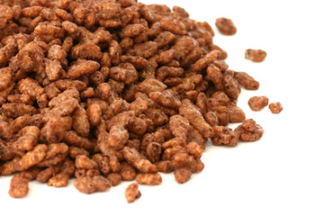 Chocolate popped rice cereals scattered on white background