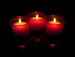 Three votive candles in red holders over black