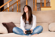Young female lose playing video-games concentrating at home