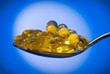 Spoon full of fish oil capsules.