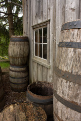 Barrels stacked against old house