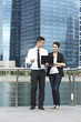 Business man and woman using a Laptop in modern urban setting
