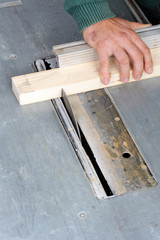Carpenter cutting wood on electric saw