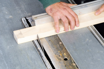 Carpenter cutting wood on electric saw
