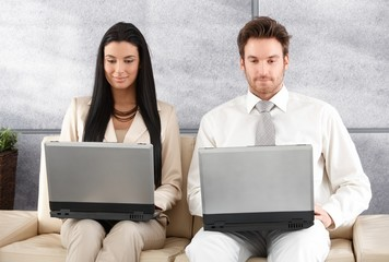 Young businesspeople sitting in office lobby