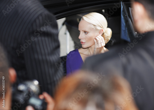 Celebrity emerging from car amid paparazzi