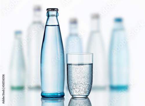 canvas print picture Mineralwasserflasche mit Glas