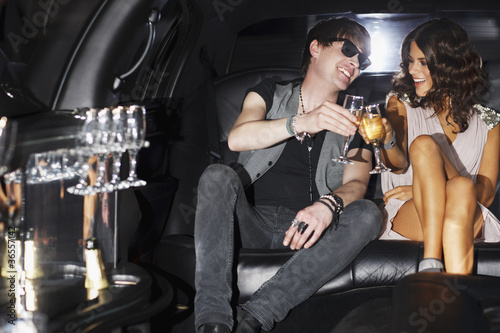 Couple toasting each other in backseat of limo
