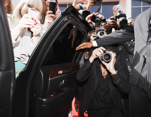 Paparazzi and fans taking photos inside car door