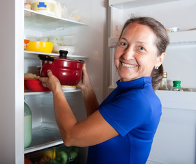 woman putting pan into refrigerator