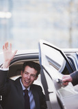 Politician waving and emerging from car