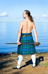 Man with naked torso in kilt